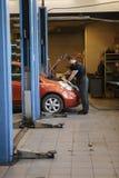 Hand av bilmekanikern med skiftnyckeln Garage för auto reparation royaltyfria foton