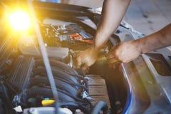 Hand av bilmekanikern med skiftnyckeln Garage för auto reparation arkivfoton