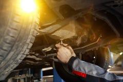 Hand av bilmekanikern med skiftnyckeln Garage för auto reparation arkivfoto