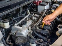 Hand av bilmekanikern som arbetar i service för auto reparation Han har den fasta gamla bilmotorn som göras strimmig med damm och royaltyfri foto