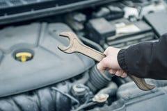 Hand av den auto mekanikern med en skiftnyckel Bilreparation hand skiftnyckeln Auto mekaniker i bilreparation arkivfoton