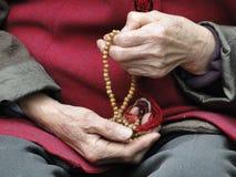 Hand av den gamla kvinnan vid bönen av radbandet arkivbild