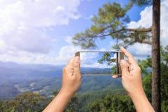 Hand av den hållande smartphonen för kvinna som tar fotoet Royaltyfri Bild