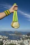 Hand av den olympiska idrottsman nen Holding Gold Medals Rio Skyline Arkivfoto