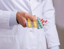 Hand av doktorer som rymmer många olika preventivpillerar Royaltyfri Foto