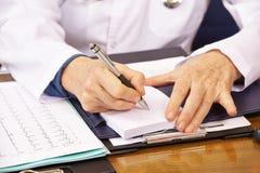 Hand av doktorn som tar anmärkningar Arkivfoto