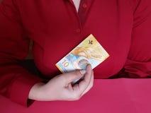 hand av en affärskvinna som rymmer en schweizisk sedel av tio franc arkivbilder