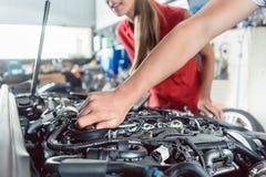 Hand av en automatisk mekaniker som kontrollerar bilen av en kund arkivfoton