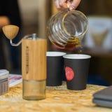 Hand av en baristaflicka som häller filtrerat kaffe in i den pappers- koppen, abstrakt logo Närbild av droppar av hällande kaffe  Royaltyfria Foton