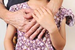 Hand av en barnomfamning händerna av en gammal kvinna med förälskelse Royaltyfri Fotografi