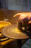 Hand av en funktionsduglig keramiker som gör en keramisk skyttel på hans hjul Fotografering för Bildbyråer