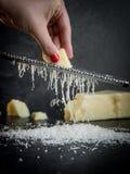 Hand av en gnisslande parmesanost f?r kvinna p? en svart bakgrund M?rk mat arkivbild
