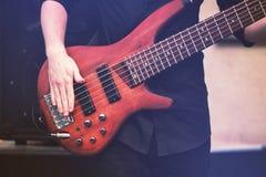 Hand av en grabb som spelar gitarren, elbas royaltyfri fotografi