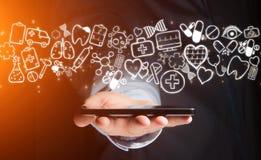 Hand av en hållande smartphone för man med medicinska symboler lite varstans Arkivbild