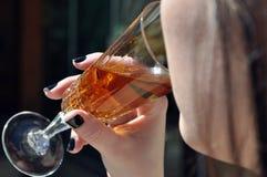 Hand av en kvinna som rymmer ett exponeringsglas och dricka Arkivfoton