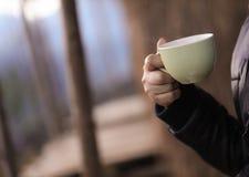 Hand av en kvinna som rymmer en kopp av grönt kaffe Royaltyfri Bild