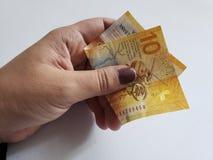 hand av en kvinna som rymmer en schweizisk sedel av tio franc arkivfoton