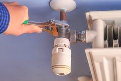 Hand av en man, repairman, closeup för installationselementventil royaltyfri fotografi