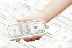 Hand av en man som rymmer 100 dollarräkningar Arkivfoton
