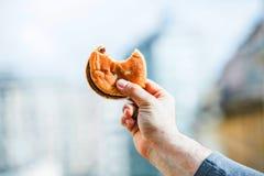 Hand av en man som rymmer en biten smörgås royaltyfria foton