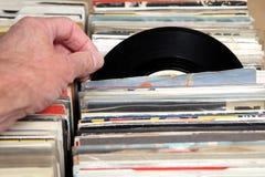 Hand av en man som ser vinyl 7& x22; singel 45 r-/min.rekord som är till salu på en retro rekord- mässa Arkivfoto