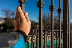 Hand av en person som fångar ett staket arkivfoton