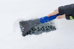 Hand av en skrapande snö för kvinna och is från bilvindrutan Royaltyfri Foto