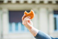 Hand av ett maninnehav/uppvisning av en biten smörgås arkivfoton