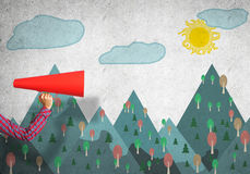 Hand av för apelsinpapper för kvinna den hållande trumpeten mot illustrerad bakgrund Arkivbild