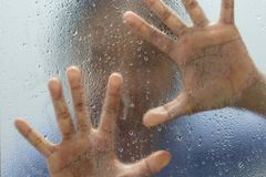 Hand av främlingen på frostat exponeringsglas med vattendroppe Arkivbild