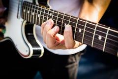 Hand av gitarristen på den elektriska gitarren Royaltyfri Foto
