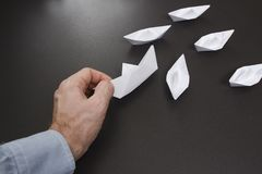 Hand av hjälp i affärsidé affärsmannen lyfter det stupade origamifartyget från vitbok Pappersskepp och affärsläge arkivbild