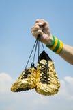 Hand av idrottsman nenHolding Gold Running skor royaltyfria bilder