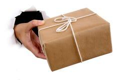 Hand av kuriren eller postmannen som levererar eller ger jordlotten till och med sönderriven vitbokbakgrund Royaltyfri Foto