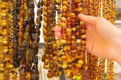 Hand av kvinnan med skinande kvinnliga bärnstensfärgade halsband på stall på basaren royaltyfri bild
