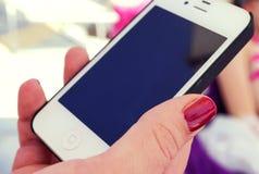 Hand av kvinnan med smartphonen Arkivfoto
