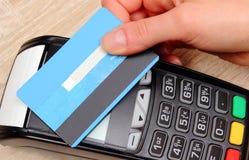 Hand av kvinnan som betalar med den contactless kreditkorten med NFC-teknologi, finansbegrepp Fotografering för Bildbyråer