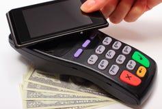Hand av kvinnan som betalar med NFC-teknologi på mobiltelefonen Arkivfoto