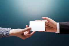 Hand av kvinnan som ger ett tomt affärskort till affärsmannen, Mocku arkivfoton