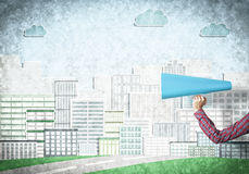 Hand av kvinnan som rymmer trumpeten för blått papper mot illustrerad bakgrund Arkivfoton