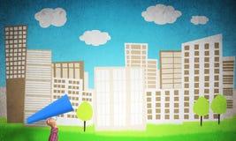 Hand av kvinnan som rymmer trumpeten för blått papper mot illustrerad bakgrund Arkivbilder