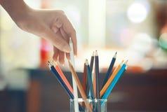 Hand av kvinnan som tar den färgade blyertspennan Arkivfoto