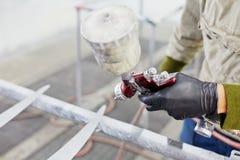 Hand av mannen med sprutmålningsfärgvapnet som målar bildetaljer Arkivbilder