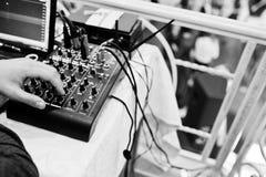 Hand av mannen på den digitala blandande konsolen kontrollera blandarepanelljudet Arkivbilder
