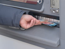 Hand av mannen som återtar pengar från en ATM Royaltyfri Bild