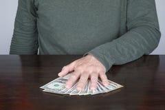 Hand av mannen som rymmer en packe av dollar Arkivfoton