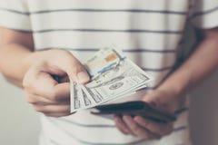 Hand av mannen som rymmer en spridning av kassa oss dollarräkning med pengar p Royaltyfri Foto