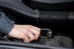 Hand av mekanikern som arbetar på en bils motor Royaltyfri Foto