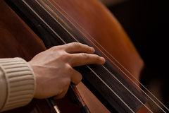 Hand av musikern på de bas- raderna Royaltyfri Bild