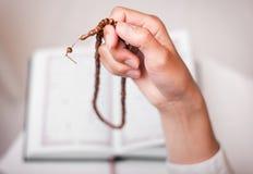 Hand av muslimflickan med radbandet Arkivfoton